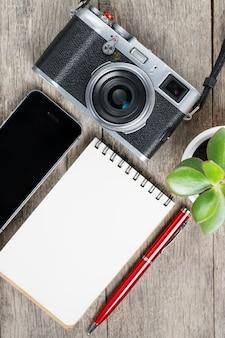 空白のメモ帳ページと電話付きの灰色の木製、ビンテージデスクに赤ペンでクラシックカメラ。