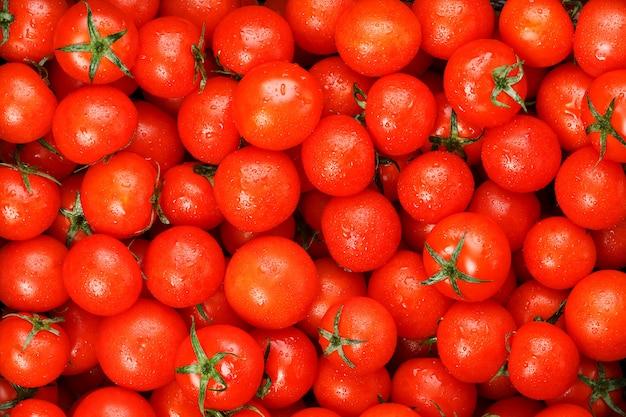露の滴と新鮮な完熟トマトがたくさん。緑の尾を持つ赤いハートのクローズアップテクスチャ。フレッシュチェリートマト