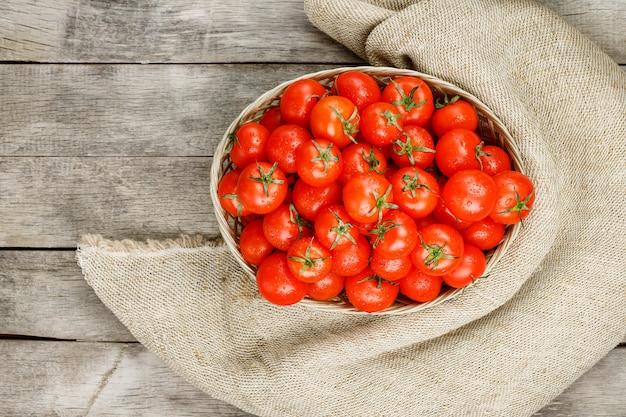 古い木製のテーブルの枝編み細工品バスケットに小さな赤いトマト。熟したジューシーなチェリー