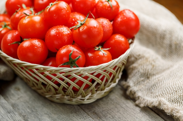古い木製のテーブルの枝編み細工品バスケットで新鮮な赤いトマト。黄麻布の周りの水分、灰色の木製テーブルの滴と熟したジューシーなチェリートマト。素朴なスタイルで。