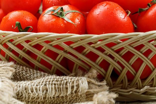 枝編み細工品バスケットで水分の滴と熟したジューシーなチェリートマト。黄麻布のキャンバスの周りの古い木製のテーブル