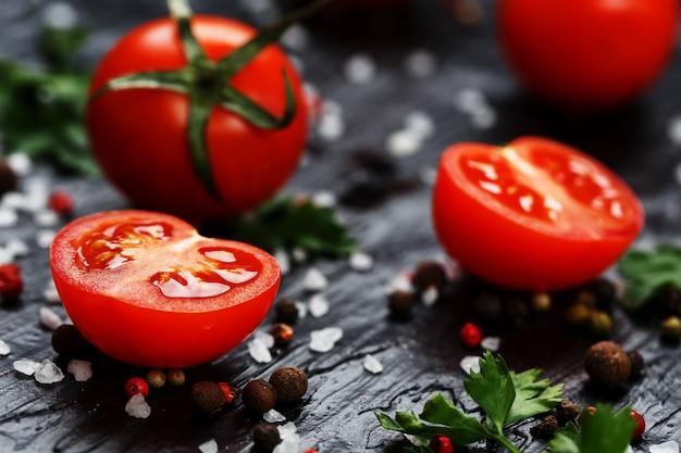 Свежие нарезанные помидоры черри со специями, крупной солью и зеленью