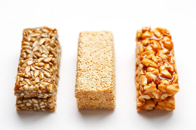 Зерновой батончик с арахисом, кунжутом и семечками в ряд. вид сверху три ассорти бара, изолировать