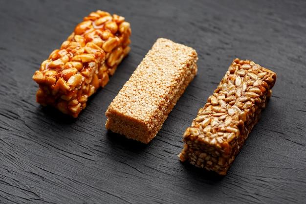 Зерновые гранола бар с арахисом, кунжутом и семечками на разделочную доску на темном каменном столе. вид сверху. три ассорти бара
