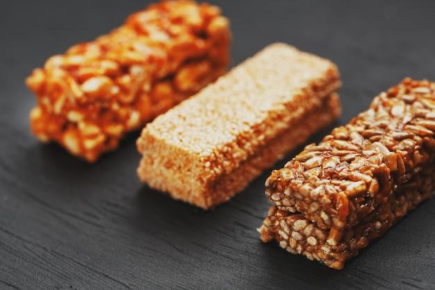 Полезные перекусы. фитнес диетическое питание. зерновой батончик с арахисом, кунжутом и семечками на разделочной доске на темном столе, энергетические батончики
