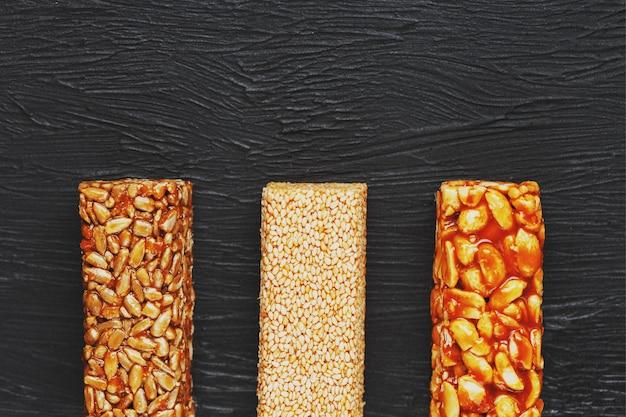 健康的なスナック。フィットネスダイエット食品。ピーナッツ、ゴマ、暗いテーブル、まな板の上の種子の粒バー、エネルギーバー