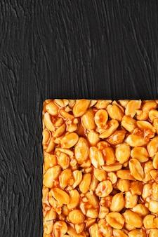Золотистый козинак из жареных арахисовых бобов энергии баров. черный текстурный фон, вид сверху