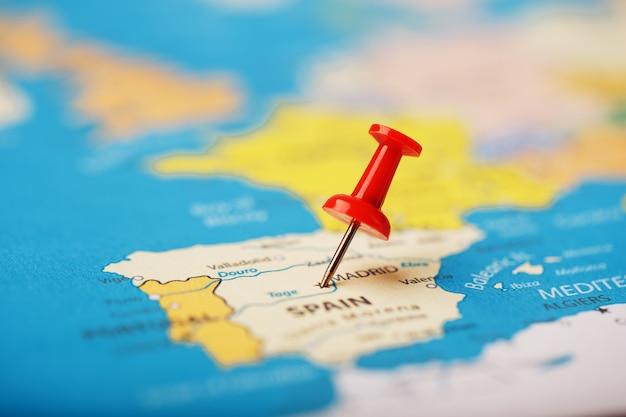 Местоположение пункта назначения на карте испании обозначено красной канцелярской кнопкой. испания отмечена на карте красной кнопкой