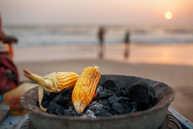グリルで石炭のゴールデンコーンの穂軸。日没時のアランボルビーチ。アジア、インドの屋台