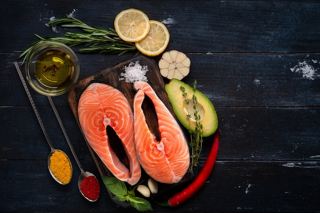 Сырой свежий стейк из лосося с травами, авокадо, базиликом, лимоном и чесноком