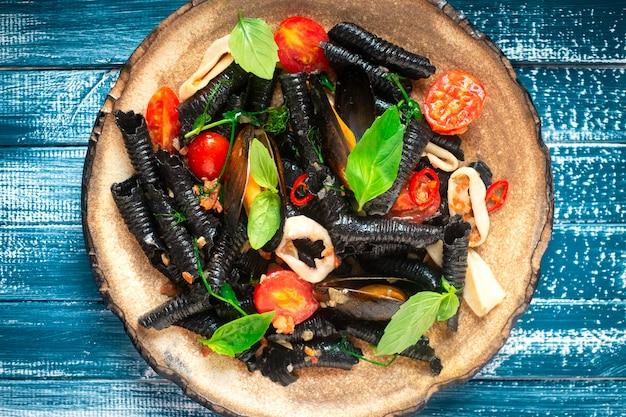 Традиционная итальянская черная паста с мидиями, томатами и морскими гребешками