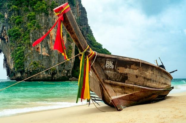 熱帯のビーチ、ターコイズブルーの水、美しい砂の木製のロングテールボート