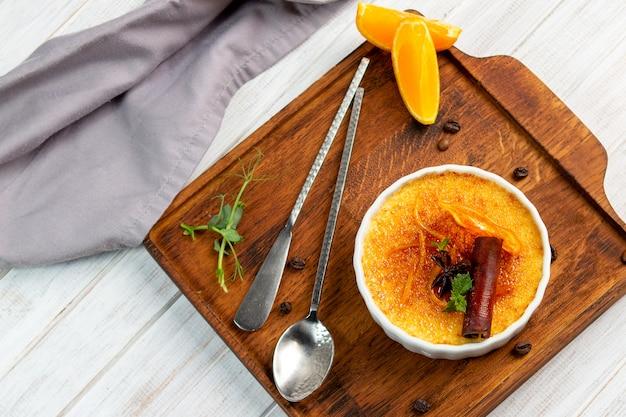 Французский десерт ванильный крем-брюле в керамической миске на деревянной доске, вид сверху