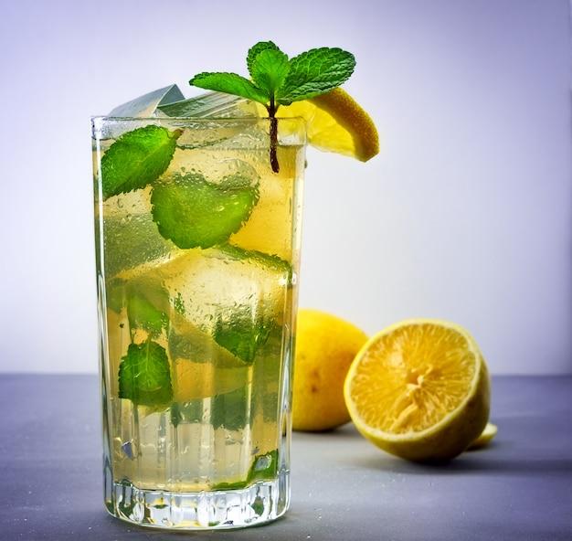 Холодный освежающий летний лимонад в стакане на сером фоне