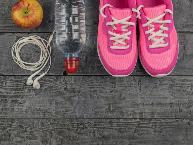 美しいピンクのスニーカー、ヘッドフォン、水、木の床にリンゴ。上からの眺め。