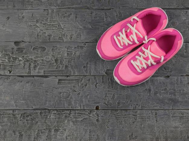 Красивые розовые женские кроссовки темный винтаж на полу. вид сверху.