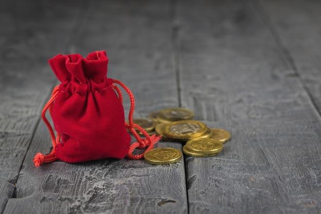 木製のビンテージテーブルの上のコインと赤いベルベットのポーチ。
