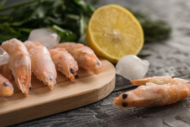 木製のテーブルにまな板の上のハーブとレモンの冷凍エビ。