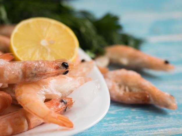 木製テーブルの上のレモンとパセリと陶器の白いボウルで冷凍エビ。