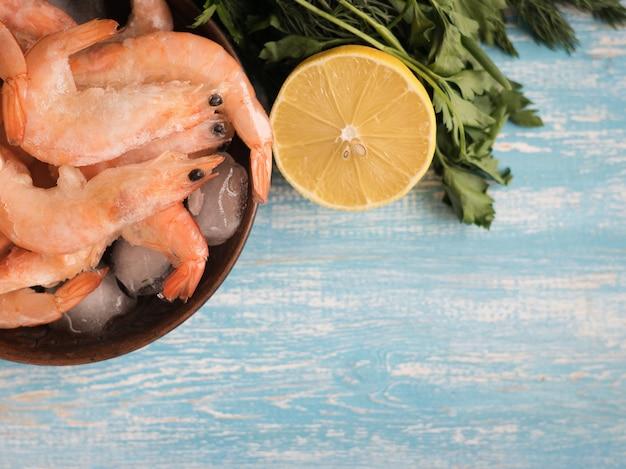 青い木製のテーブルにパセリとレモンの陶器の白いボウルに冷凍エビ。