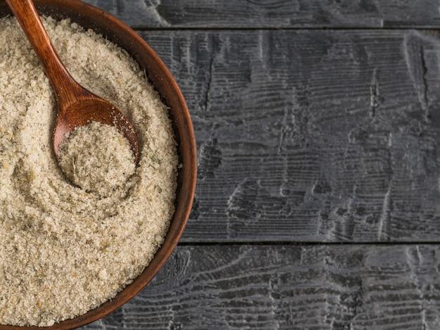 木製テーブルの上のハーブと塩で満たされたスプーンで粘土ボウル。