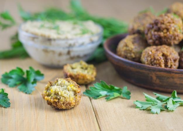 Свежеприготовленный фалафель на листьях салата на столе с соусом тахини