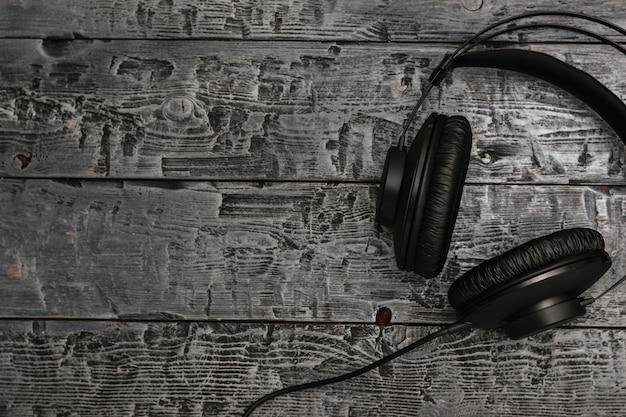 黒い木製のテーブルの上のワイヤーと黒のヘッドフォン。