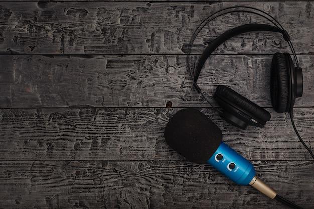 Синий микрофон с черным проводом и черные наушники на черном деревянном столе.