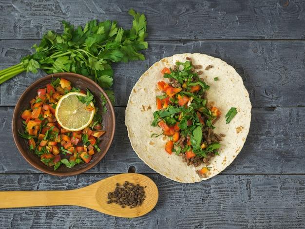 暗い木製のテーブルでメキシコのタコス、ベジタリアンサラダ、スパイスを調理するトルティーヤ