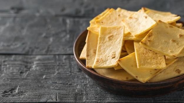 黒い木製のテーブルの上に粘土ボウルにチーズとメキシコのトルティーヤチップ。