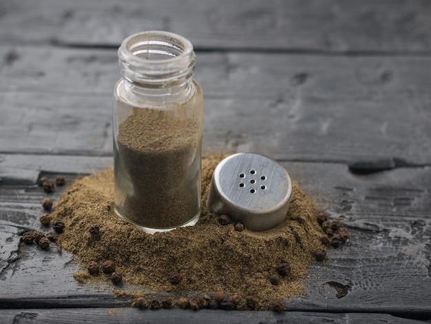 素朴なテーブルに挽いたコショウの開いた瓶。