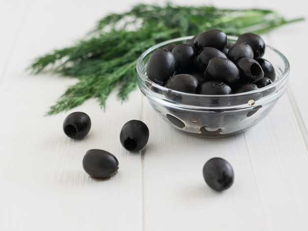 Оливки в стеклянную емкость и большой пучок укропа на белом столе.