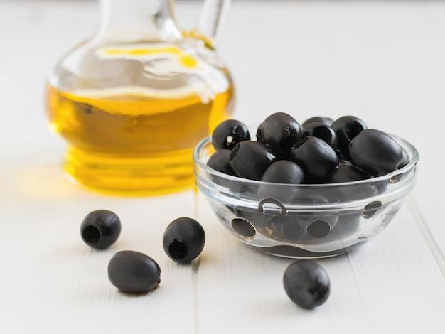 Чашка с разбросанными оливками и бутылка оливкового масла на белом столе.