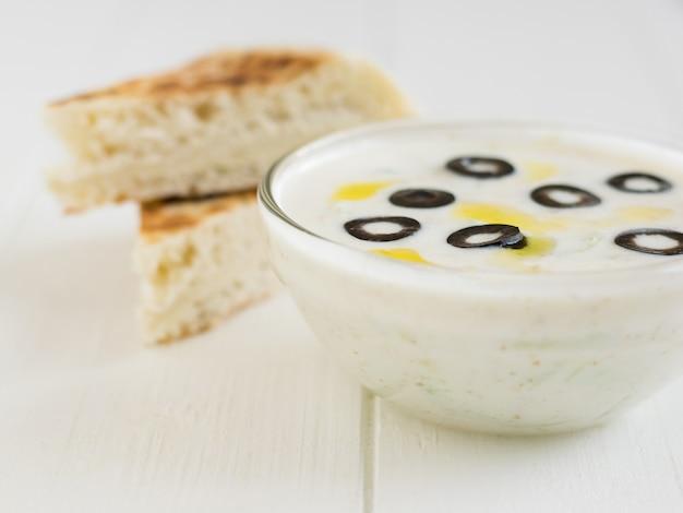 Два куска хлеба и цацики в миску с оливками на белом деревянном столе.