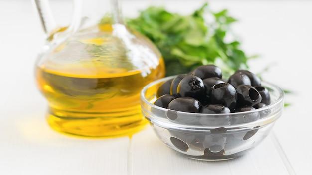Оливки, зелень и бутылка оливкового масла на белом столе