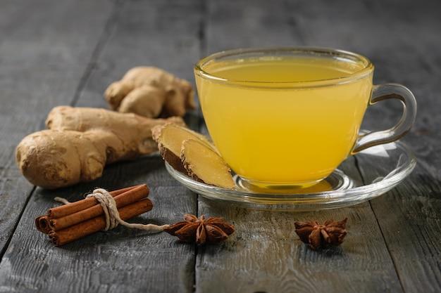 生姜の根と柑橘類の飲み物とシナモンの束は、黒い木製のテーブルに貼り付けます。