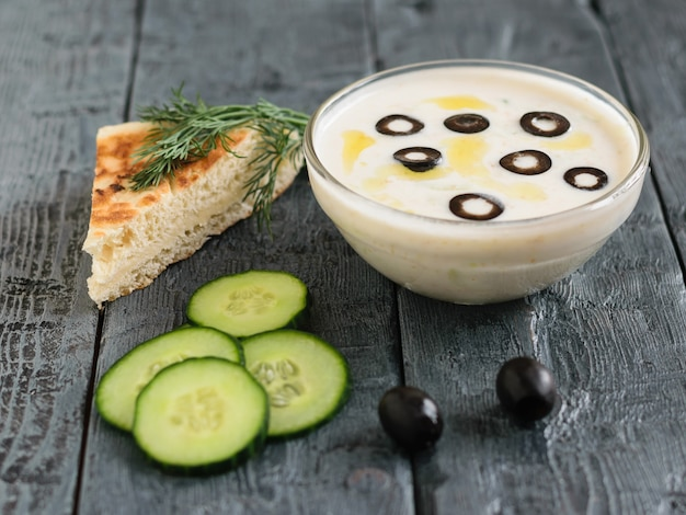 Соус цацики в стеклянной посуде и оливки на темном деревянном столе с куском хлеба