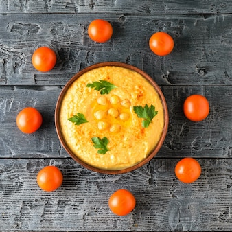Чаша со свежим хумусом и восемью помидорами черри на деревянном столе
