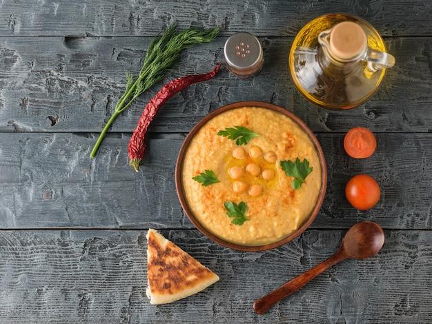 Свежий хумус, деревянная ложка, кусочек лаваша, помидоры на деревянном столе