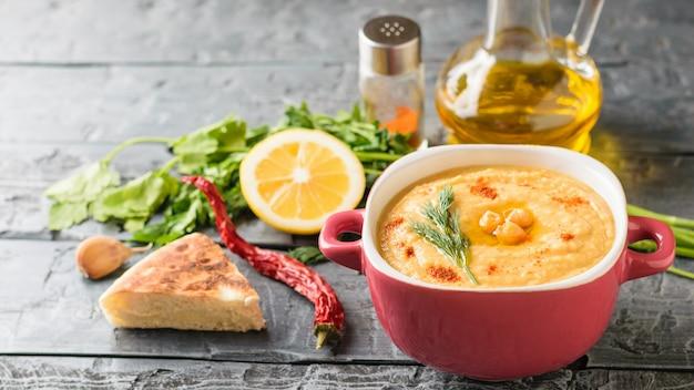Свежеприготовленный хумус в фиолетовой миске, кувшин с оливковым маслом и специями на деревянном столе