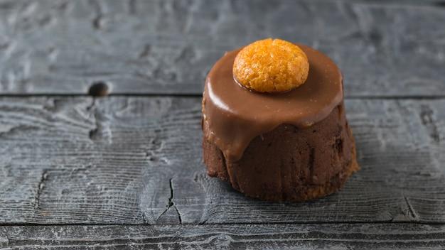 Свежий торт украшен печеньем на темном деревенском столе