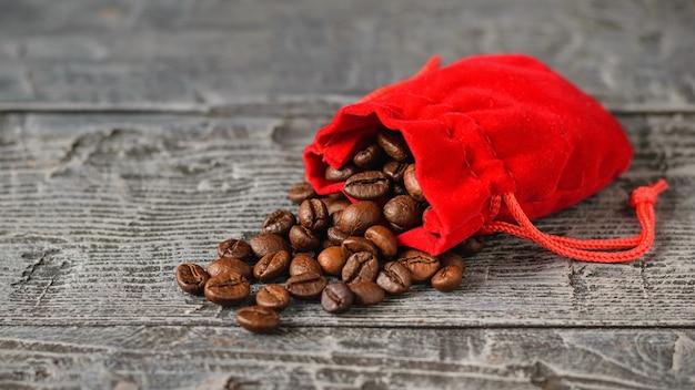 木製のテーブルの赤いバッグから注がれたコーヒー豆ダークローストコーヒー
