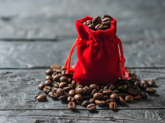 暗い木製のテーブルでローストコーヒー豆の赤いバッグ