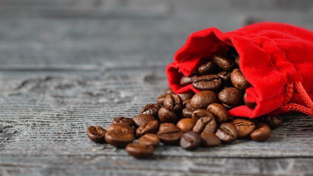 暗い素朴なテーブルに落ちたコーヒー豆の袋