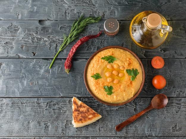Чаша со свежим хумусом, оливковым маслом, чили и помидорами черри на темном деревенском столе