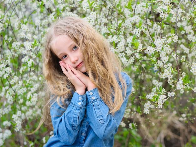 桜の庭でデニムシャツを着た髪を持つ少女