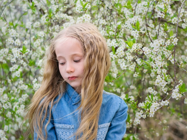 悲しそうな顔の少女が春の桜公園で頭を下げた