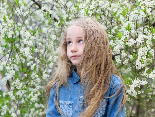 桜の公園で髪を下に向けたデニムシャツの少女の肖像画