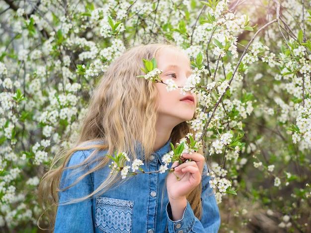 デニムシャツを着た女の子が桜の香りを楽しむ