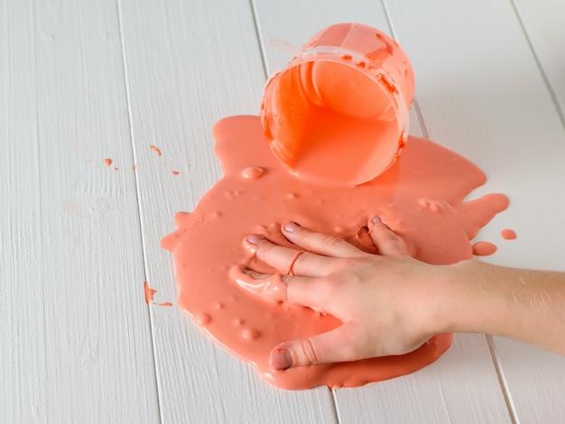 Руки ребенка размазаны по белому столу оранжевой улыбкой.